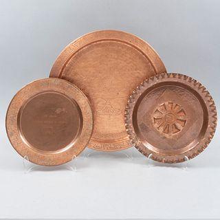 Lote de 3 platones. Siglo XX. Elaborados en cobre. Decorados con elementos frutales, geométricos, orgánicos, sol, grecas y frutero.