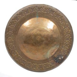 Escudo decorativo. Siglo XX. Elaborado en laton martillado. Decorado con elementos vegetales y orgánicos cincelados.