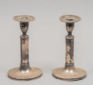 Par de candeleros. Siglo XX. Elaborados en plata laminada. Con arandelas circulares. 18 x 10 cm. Ø