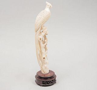 Ave sobre ramas. Origen oriental, siglo XX. En talla de marfil . Con base de madera.