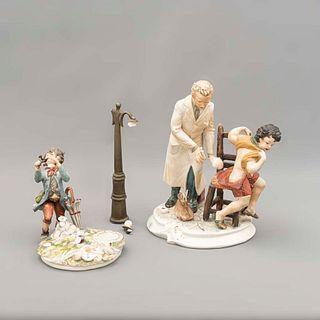 Lote de 2 figuras. Italia. Siglo XX. Elaboradas en porcelana Capodimonte. Consta de: Doctor y Niño con resortera.