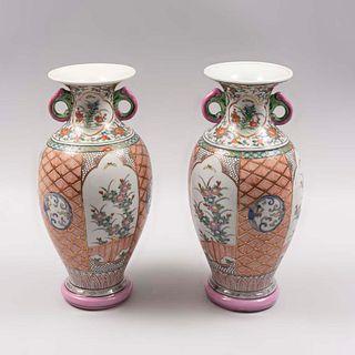 Par de jarrones. Siglo XX. Estilo Familia Rosa. Elaborados en cerámica. Decorados con motivos florales y orgánicos. 31 cm altura