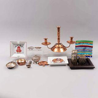 Lote de 14 piezas. SXX. En alpaca, metal, cobre, porcelana, vidrio, cristal y madera. Consta de: candelabro, taza, 3 ceniceros, otros.