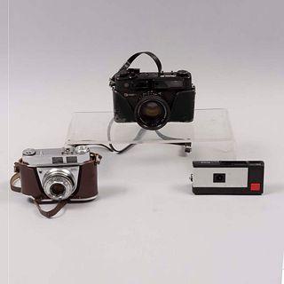 Lote de 3 cámaras fotográficas. Siglo XX. Elaboradas en metal, baquelita y material sintético. Marca Yashica y Kodak.