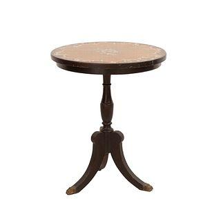 Mesa. Siglo XX.  En talla de madera. Con cubierta circular, fuste compuesto y soportes con casquillos de metal dorado.