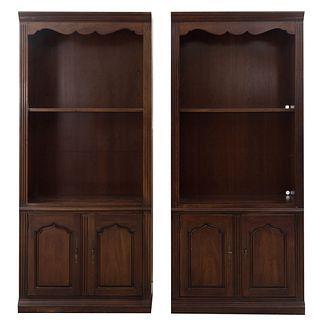 Par de libreros. Siglo XX Elaborados en madera. Con espacio para entrepaños, 2 puertas abatibles y soportes tipo zócalo.