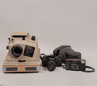 Lote de 2 cámaras fotográficas y proyector con estuche. Siglo XX. Elaboradas en metal, baquelita y material sintético.