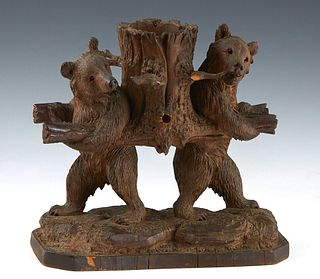 Carved Black Forest Pipe Holder, 19th c., with two standing bears supporting a basket, the outside of the basket with holders for three pipes, H.- 10