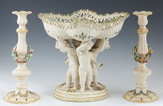 Dresden Style Three Piece Earthenware Garniture Set, 19th c., consisting of a reticulated undulating center bowl upheld by three putti, on an integral