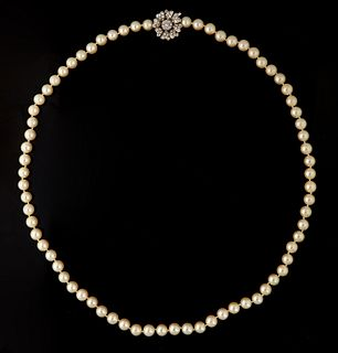 Strand of 7.8 mm White Cultured Pearls, with a 14K floriform white gold clasp/enhancer, the center mounted with a 15 point round diamond surrounded on
