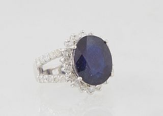 "Lady's 14K White Gold Dinner Ring, with an oval 8.97 ct. blue sapphire atop a border of round diamond ""points,"" on a split shoulder band mounted with"