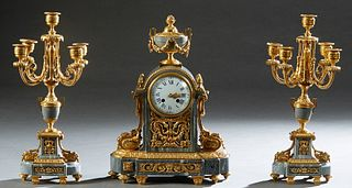 Three Piece French Louis XVI Style Gilt Bronze and Gray Marble Clock Set, 19th c., the clock with a marble urn surmount over an enamel dial time and s