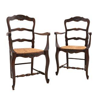 Par de sillones. Francia. Siglo XX. Estilo Luis XV. En talla de madera de roble. Con respaldos escalonados y asientos de palma tejida.
