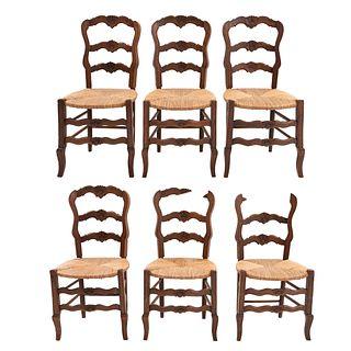 Lote de 6 sillas. Francia. Siglo XX. Estilo Luis XV. En talla de madera de roble. Con respaldos escalonados y asientos de palma.