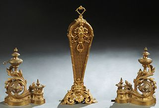 Three Brass Fireplace Items, 20th c., consisting of a pair of Louis XVI style gilt brass chenets with urn form tops issuing from pierced swirled leaf