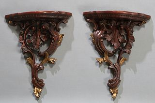 Pair of Carved Mahogany Bracket Shelves, 20th/21st c., the serpentine top on a pierce carved leaf and acorn support with gilt highlights, H.- 17 in.,