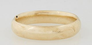 Lady's 18K Victorian Style Hinged Bangle Bracelet, 20th c., with leaf engraving, Int. H.- 2 in., W.- 2 1/4 in., Wt.- .71 Troy Oz. Provenance: The Esta