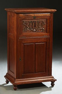 American Carved Mahogany Music Cabinet, late 19th c., the stepped rounded edge top over a fall front enclosing two shelves, above a lower cabinet door