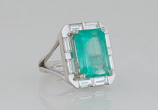 Lady's Platinum Dinner Ring, with a 6.52 carat emerald atop a border of eight .2 ct. baguette diamonds, on a split sided U-shaped band, Total diamond