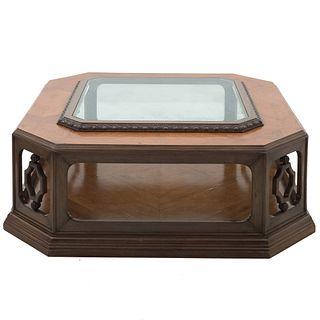 Mesa de centro. Siglo XX. Elaborada en madera enchapada. A dos niveles. Con cubierta octagonal, con vidrio. Soporte tipo zócalo.