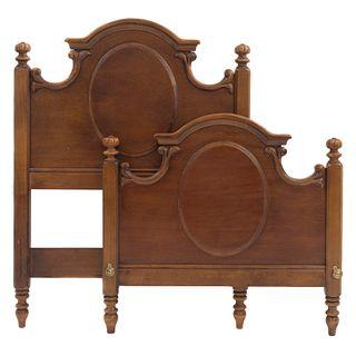 Cama individual. Siglo XX. Elaborada en madera. Consta de: cabecera y piecera. Con fustes lisos y soportes tipo carrete.