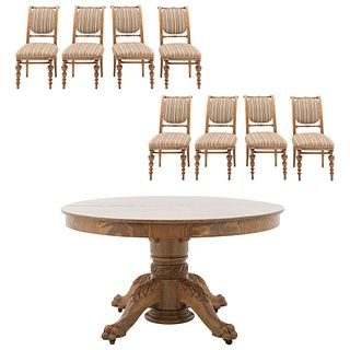 Comedor. Siglo XX. Elaborado en madera tallada y enchapada. Consta de: Mesa. Con cubierta circular, fuste anillado y 8 sillas.
