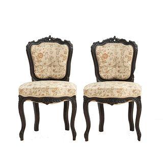 Par de sillas. SXX. Elaboradas en madera tallada. Con respaldos, asientos en tapicería de tela con motivos florales.