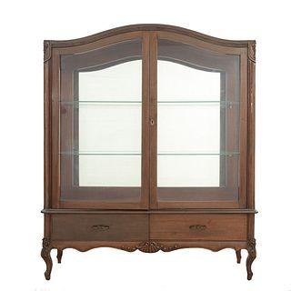 Vitrina. Siglo XX. En talla de madera. Con 2 puertas abatibles, paredes y entrepaños interiores de cristal, 2 cajones