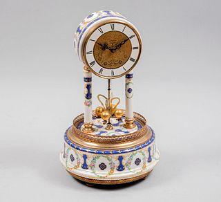 Reloj de mesa. Alemania. Siglo XX. Elaborado en cerámica y metal dorado. Mecanismo de péndulo. Con carátula circular.