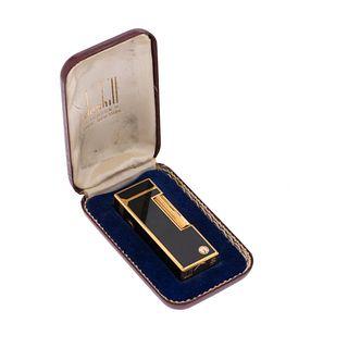 Encendedor Dunhill. Cuerpo en acero dorado con esmalte color negro. Estuche original.