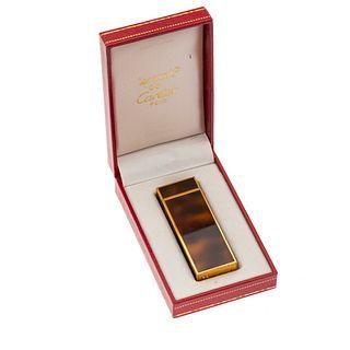 Encendedor Cartier Must. Cuerpo en acero dorado, acabado marmoleado. Estuche original.