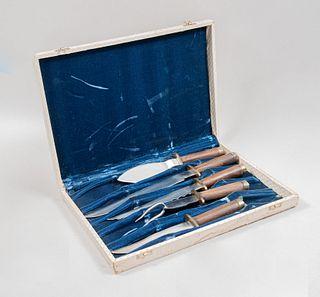 Juego de 5 cubiertos de servicio. Siglo XX. Elaborados en acero. Con detalles en madera y metal dorado. En caja.