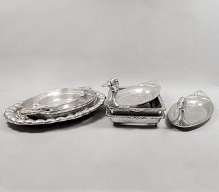 Lote de 7 piezas. Diferentes orígenes y diseños. Siglo XX. Elaborados en pewter. Consta de: 5 charolas y 2 porta refractarios.