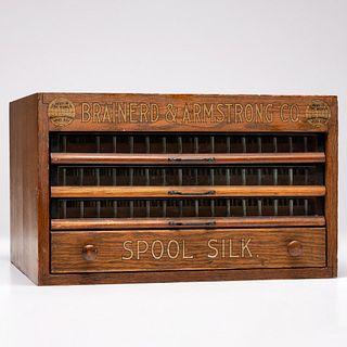 A Brainerd & Armstrong Co. Stenciled Tabletop Oak Spool Cabinet