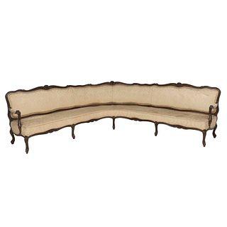 Sala esquinera. Siglo XX.  Talla en madera. Con respaldo cerrado y asiento en tapicería color beige.