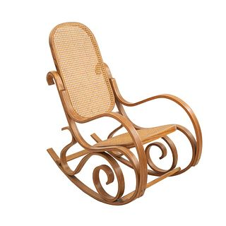 Mecedora. Siglo XX. Estilo austriaco. Talla en madera. Con respaldo cerrado y asiento de ratán y fustes a manera de roleo.