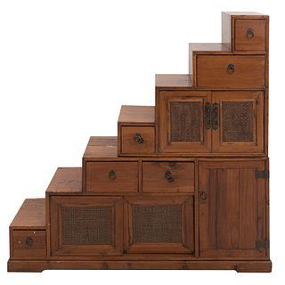 Cómoda. SXX. Diseño a manera de escalera. En madera entintada. A 2 cuerpos. Con 5 puertas y 6 cajones con tiradores. 130 x 132 x 39 cm