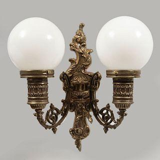 Arbotante. Siglo XX. Elaborado en pewter. Para 2 luces. Con pantallas de vidrio lechoso, fuste compuesto y brazos a manera de roleos.