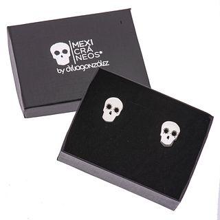Par de mancuernillas en metal base de la firma Delia González de la colección MexiCráneos. Peso: 8.0 g. Estuche original.