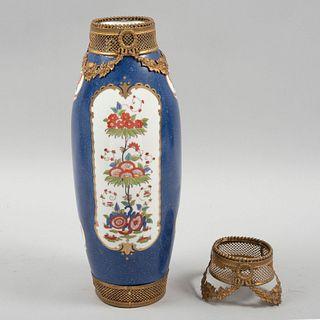 Florero. Siglo XX. Elaborado en porcelana. Decorado con motivos vegetales, florales, orgánicos, aplicaciones de metal dorado.