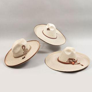 Lote de 3 sombreros de faena. México. Siglo XX. Elaborados en palma tejida. Decorados con toquilla.