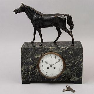 Reloj de chimenea. Siglo XX. Elaborado en bronce y mármol verde jaspeado. Mecanismo de cuerda. Decorado con caballo.