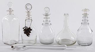 Five colorless glass decanters and wine taster