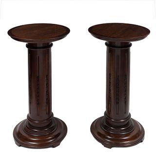 Par de pedestales. Siglo XX. Talla en madera de caoba. Con capitel circular, fuste acanalado y soporte circular.
