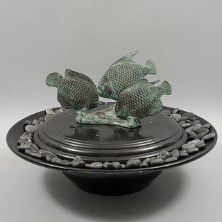 Fuente. SXX. Elaborada en metal. Con decoración de peces en bronce y piedras. 60 cm de diámetro.