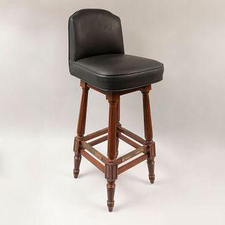 Silla para barra. Siglo XX. Estilo Enrique II. Con respaldo y asiento en tapicería de vinipiel. Sistema giratorio.