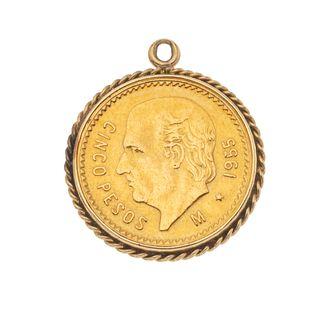 Pendiente con moneda de cinco pesos en oro amarillo de 21.6k. Bisel torzal en oro amarillo de 14k. Peso: 5.1 g.