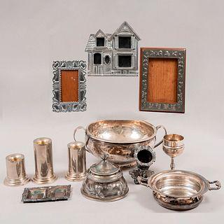 Lote mixto de 11 piezas. Consta de:3 portarretratos, 3 candeleros, copa, tintero, charola miniatura, centro de mesa y depósito con tapa