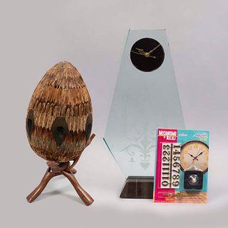 Lote mixto: Consta de: a) Reloj de mesa. SXXI. Elaborado en vidrio. b) Huevo decorativo. Elaborado en cerámica.