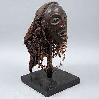 Máscara africana. SXX. Talla de madera. Decorada con hilo entretejido, conchas y cuentas. En base de madera.